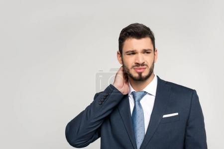 young businessman suffering from pain in neck and looking away isolated on grey