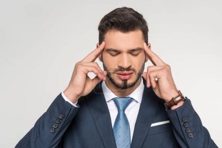 jeune homme d'affaires élégant souffrant de maux de tête isolé sur fond gris