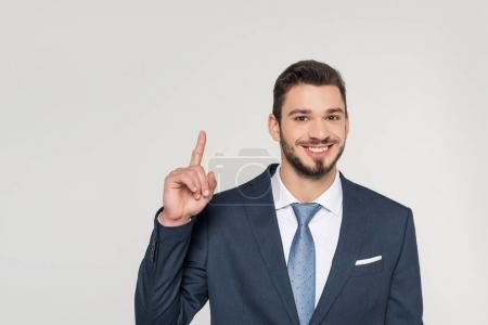 Photo for Smiling young businessman pointing up with finger and looking at camera isolated on grey - Royalty Free Image
