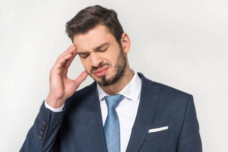 jeune homme d'affaires, souffrant de maux de tête isolé sur fond gris