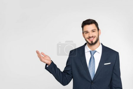 handsome young businessman showing copy space and smiling at camera isolated on grey