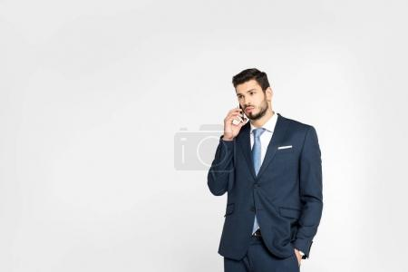 stylish young businessman standing with hand in pocket and talking on smartphone while looking away isolated on grey
