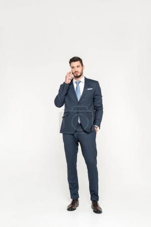 full length view of stylish young businessman standing with hand in pocket and talking on smartphone isolated on grey