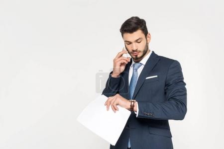 Photo for Young businessman holding papers and talking on smartphone while checking wristwatch isolated on grey - Royalty Free Image