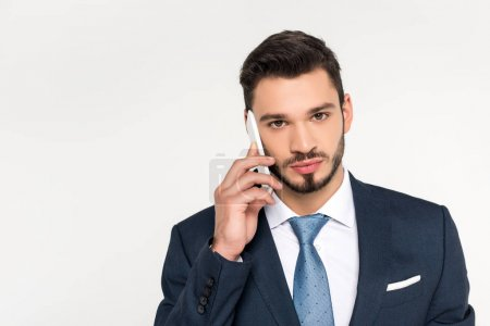 handsome young businessman talking on smartphone and looking at camera isolated on grey
