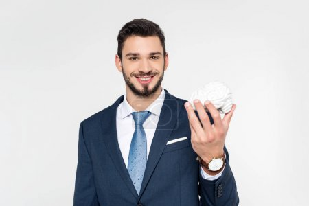 young businessman holding brain model and smiling at camera isolated on grey