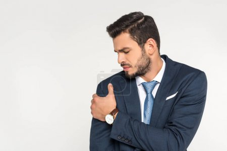 young businessman suffering from pain in arm isolated on grey