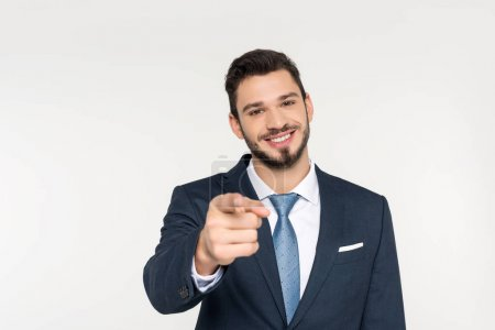 smiling young businessman pointing at camera isolated on grey