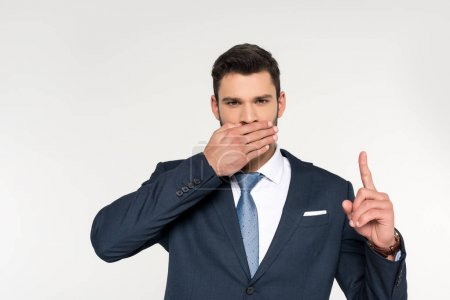 young businessman closing mouth with palm and pointing up with finger isolated on grey