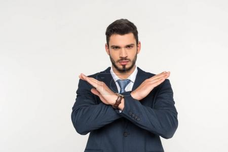 serious young businessman crossing hands and looking at camera isolated on grey