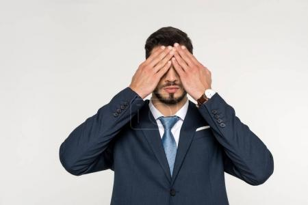 young businessman closing eyes with hands isolated on grey
