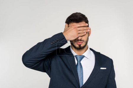 young businessman closing eyes with palm isolated on grey