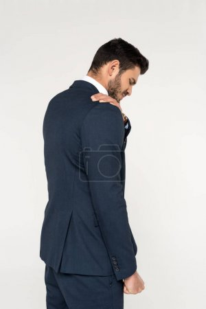 back view of young businessman suffering from ache in shoulder isolated on grey