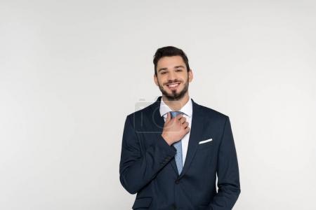 Foto de Guapo joven empresario ajustando la corbata y sonrisa en cámara aislada en gris - Imagen libre de derechos