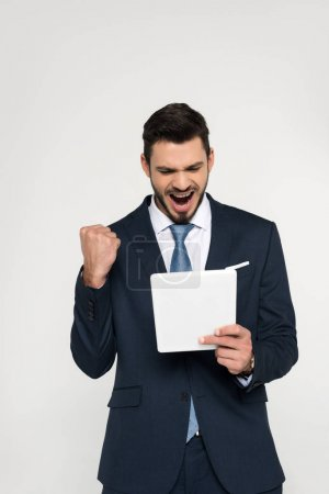 triumphing young businessman holding digital tablet isolated on grey