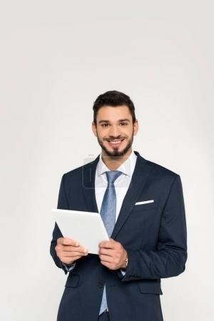 Photo for Handsome young businessman holding digital tablet and smiling at camera isolated on grey - Royalty Free Image