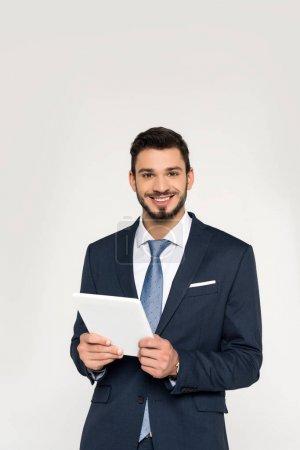 Foto de Guapo joven empresario sosteniendo la tableta digital y sonriendo a cámara aislada en gris - Imagen libre de derechos