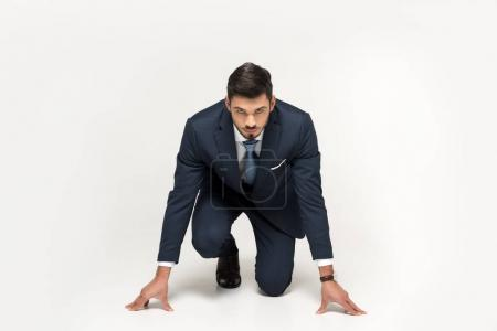 Photo for Serious young businessman in starting position ready to run isolated on grey - Royalty Free Image
