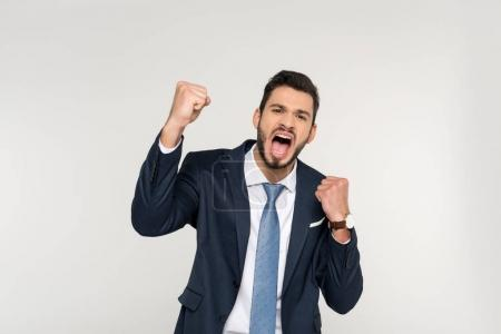 excited young businessman shaking fists and screaming at camera isolated on grey
