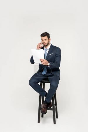 serious young businessman talking on smartphone and reading papers while sitting on stool isolated on grey