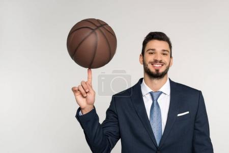 young businessman holding basketball ball on finger and smiling at camera isolated on grey