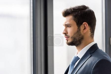 Photo for Side view of handsome young businessman looking at window - Royalty Free Image