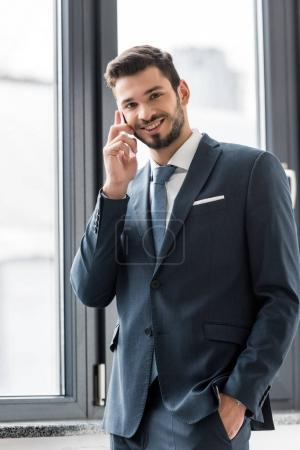 young businessman talking on smartphone and smiling at camera in office