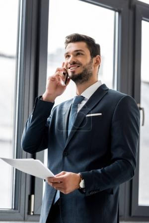 smiling young businessman holding papers and talking on smartphone in office
