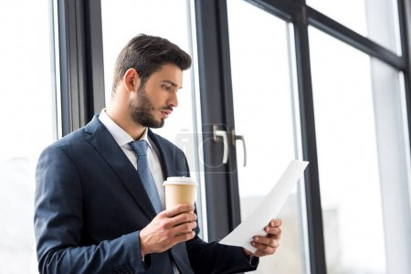Photo pour Jeune entrepreneur détenant le café pour aller et lire des documents au bureau - image libre de droit
