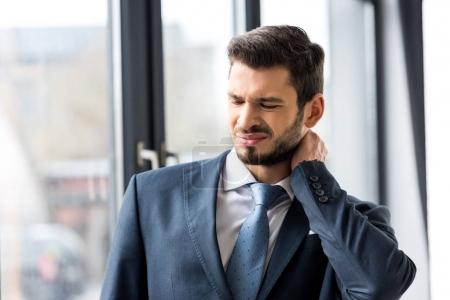 young businessman suffering from pain in neck