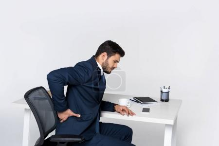 young businessman suffering from backache while sitting at workplace