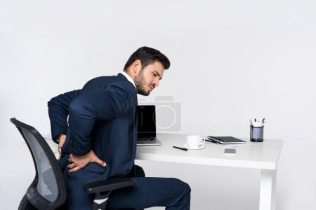 young businessman suffering from pain in back while sitting at workplace