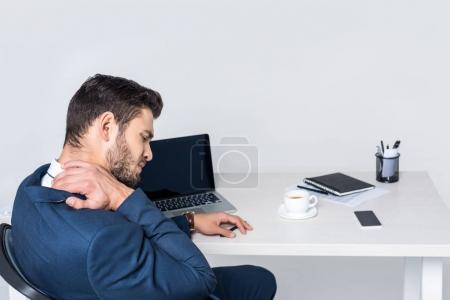 young businessman suffering from pain in neck while sitting at workplace