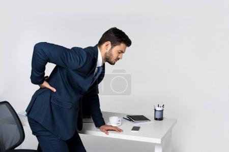 side view of young businessman suffering from backache and leaning at office table