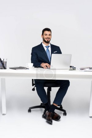 handsome young businessman smiling at camera while using laptop at workplace