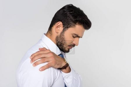side view of young overworked businessman having backache isolated on grey