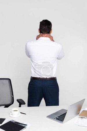 back view of young businessman suffering from pain in neck while standing at workplace