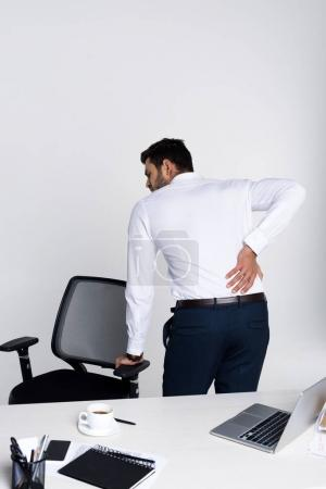 young businessman suffering from backache while leaning at chair in office