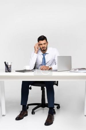 young businessman suffering from headache while sitting at workplace