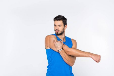 handsome sporty man stretching hands and looking away isolated on white