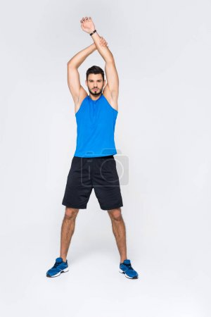 full length view of handsome sporty man stretching hands and looking at camera isolated on white