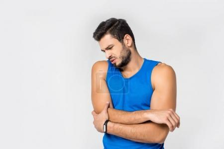 sportive young man with arm pain isolated on white