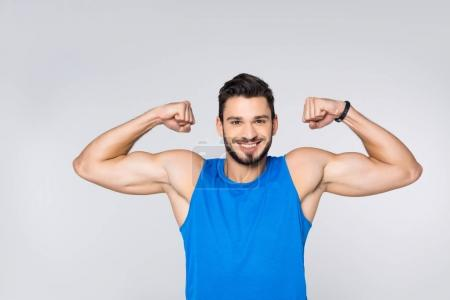 happy young man showing biceps isolated on white
