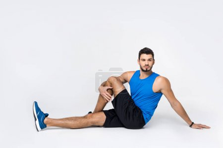 Photo for Handsome young man stretching leg while sitting on white - Royalty Free Image