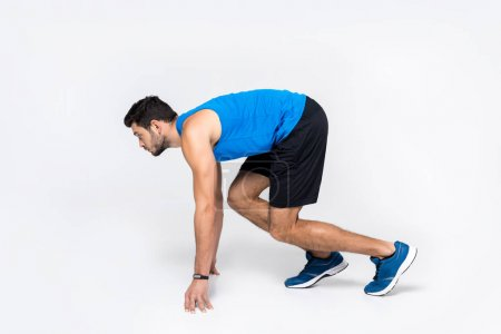 Photo for Side view of young runner in start position on white - Royalty Free Image