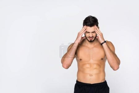 shirtless young sportive man with headache isolated on white