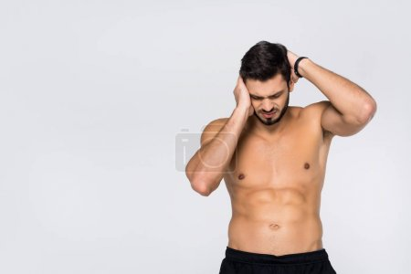 shirtless young athletic man with headache isolated on white
