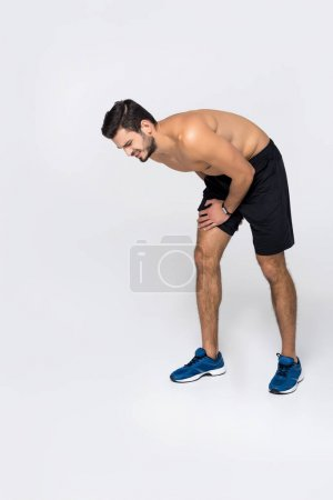sportive shirtless man with pain in leg isolated on white