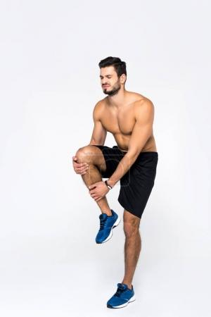 athletic shirtless man with knee pain isolated on white