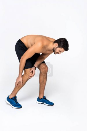 sportive young man with knee pain on white